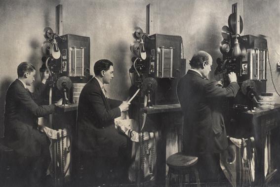 Los fotógrafos  Antonio Merayo (izq.) y Alberto Etchebehere (medio) y el animador y escenógrafo Andrés Ducaud (der.) en la cabina de impresión de la Casa Valle, ca. 1920. Colección Andrea Cuarterolo